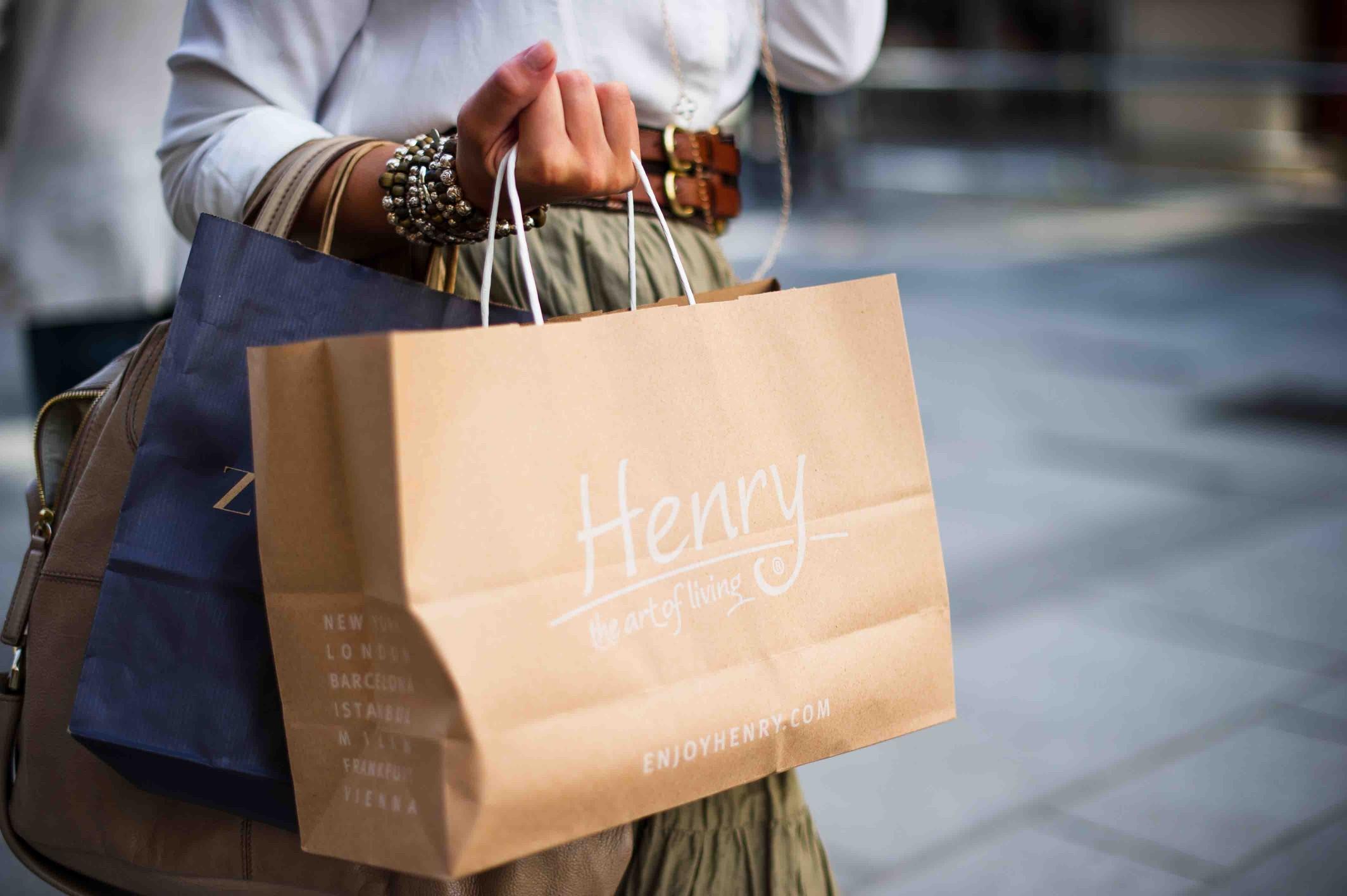 femeie care deține un sac de cumpărături de hârtie
